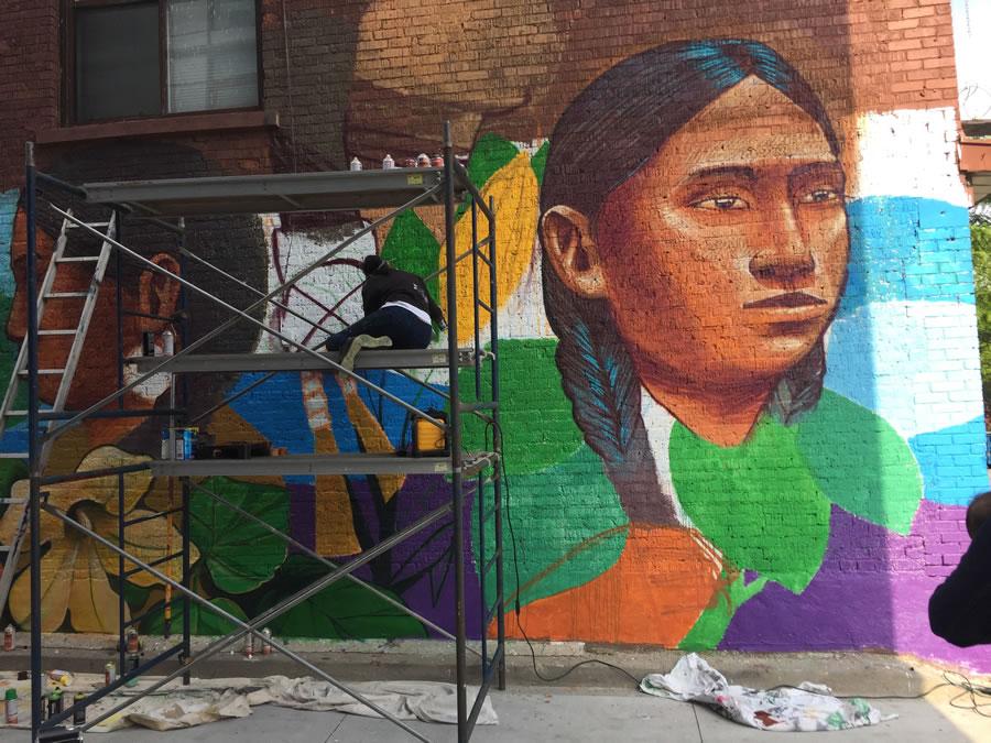 Spray artist working on mural